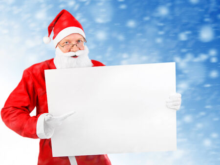 Santa Claus with Empty white Board on abstract winter background photo
