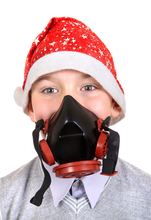 Boy in Gas Mask and Santas Hat Isolated on the White Background photo