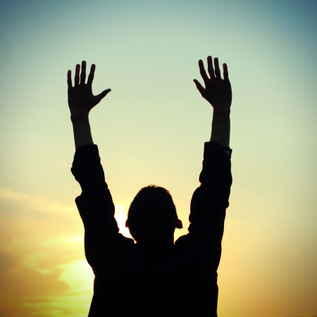 夕日の背景に祈っている人のシルエットの写真のトーン