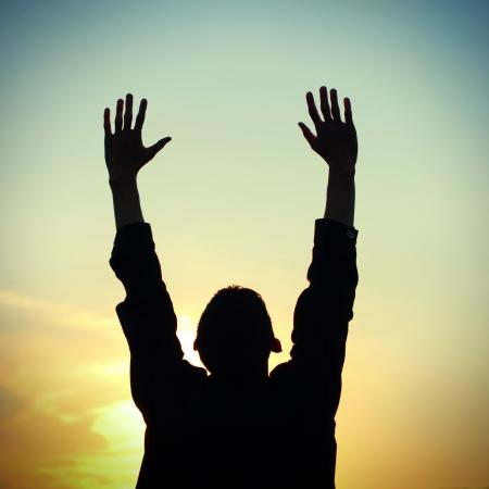 praying man: Toned photo of Praying Man silhouette on Sunset background