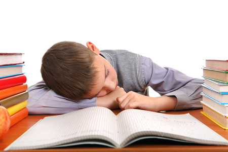 the weariness: Tired Boy Sleeping on the School Desk on the white background Stock Photo