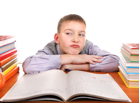 Bored Boy on the School Desk Isolated on the white background photo