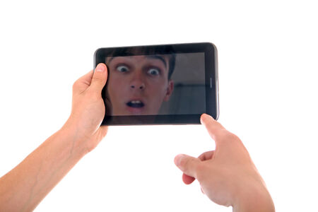 Reflection of Surprised Face in Display of Tablet Computer Isolated on the White Background photo