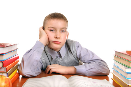 ennui: Bored Boy on the School Desk Isolated on the white background