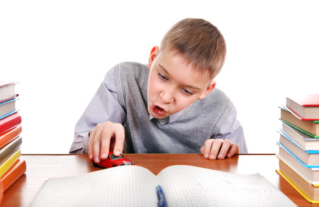 Schoolboy plays with a Toy on the School Desk on the white background photo