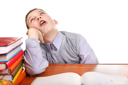 Annoyed Kid on the School Desk on the white background photo