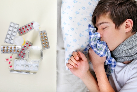 Sick Young Man sleeping on the Bed near the table with a pills Stock Photo - 25039144