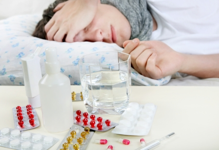 Sick Young Man sleeps with Pills on foreground. Focus on the Pills Stock Photo - 25039157