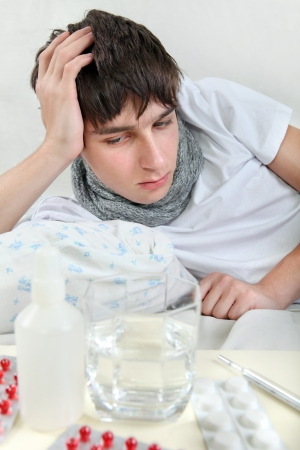 Sick Young Man lying on the Bed with Pills on foreground Stock Photo - 25039159