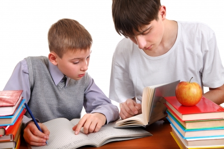helps: Older Brother helps Little Brother with a homework on the white background Stock Photo