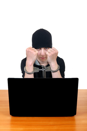 Serious Young Man in Handcuffs at the Desk with Laptop Isolated on the White photo