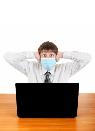 Shocked Young Man in Flu Mask at the Desk with Laptop Isolated on the White photo