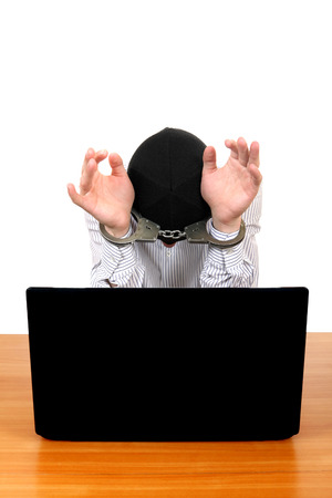 Arrested Man in Handcuffs at the Desk with Laptop Isolated on the White Background photo