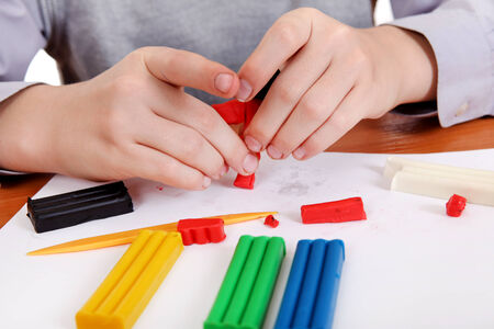 putty: Kid playing with Plasticine at the School Desk Closeup Stock Photo