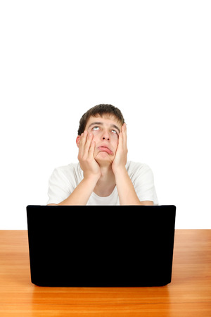 wearied: Bored and Annoyed Student at the Desk with Laptop Isolated on the White Stock Photo