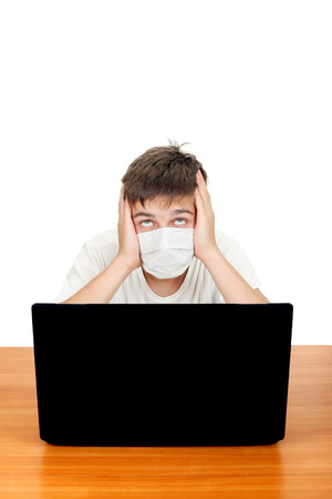 Sick Teenager in Flu Mask at the Desk with Laptop Isolated on the White Stock Photo - 25390997