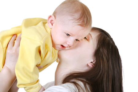 Young Mother kissing the beautiful Baby Boy Isolated on the White  photo