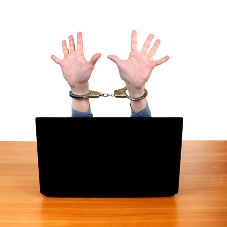 Hands in Handcuffs behind Laptop Isolated on the White  photo