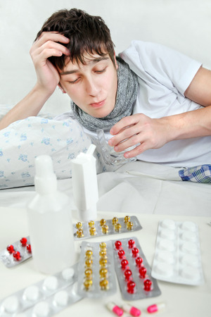 Sick Young Man taking a Pill on the Bed photo