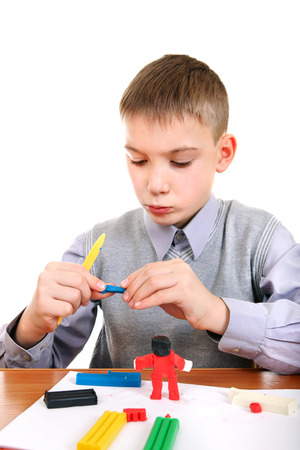 Cute Kid playing with colorful plasticine at the School Desk photo
