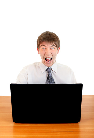 Angry Young Man is shouting at the Desk with Laptop Isolated on the White Stock Photo - 25905419