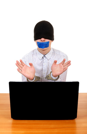 manacle: Teenager with Sealed Mouth in Handcuffs at the Desk with Laptop Isolated on the White Stock Photo