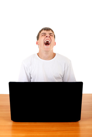 drowse: Tired Teenager Yawning at the Desk with Laptop Isolated on the White Background