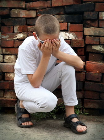 Sad Boy sit near the old brick wall photo
