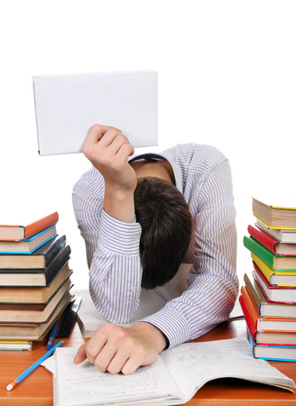 fatigued: Weary Student with the Book on the Hand at the School Desk Isolated On the White Stock Photo