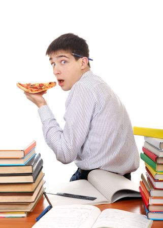 secretly: Hungry Student secretly eating a Pizza at the School Desk