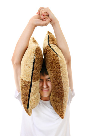 Displeased Teenager covering his Ears with Cushion Isolated On The White Background photo