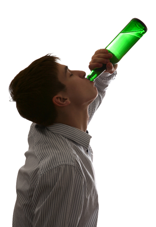 Silhouette of Young Man drinks a Beer on the White Background photo
