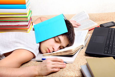 exam room: Tired Teenager sleeping on the Sofa with the Books