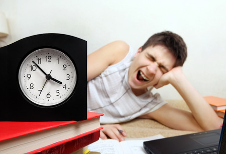 the weariness: Tired Teenager doing Homework and Yawning at the Home. Focus on the Clock