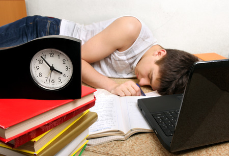 Teenager sleeping after prepare for Exam at the Home. Focus on the Clock