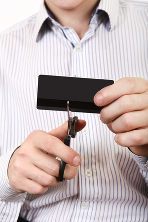 Person cutting a Credit Card Closeup on the White Background photo