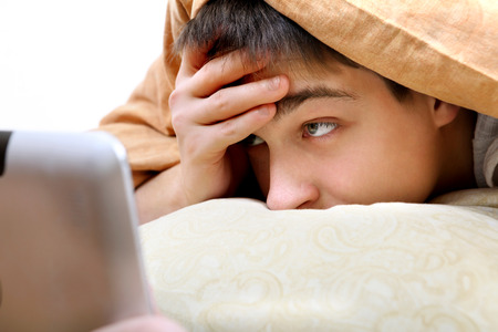 Teenager with Tablet Computer under Blanket at the Home photo