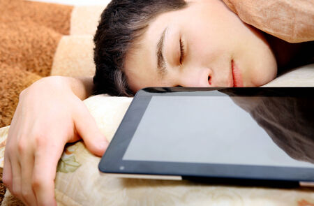 Tired Teenager sleeping at the Home with Tablet Computer photo