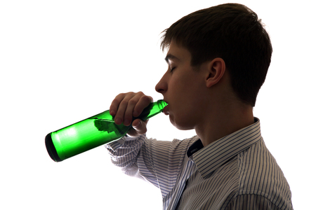 Silhouette of Teenager drinks a Beer on the White Background photo
