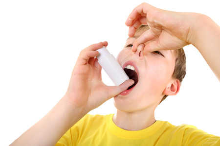 grippe: Dissatisfied Kid using Inhaler Isolated on the White Background