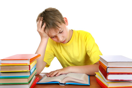 Tired Kid at the School Desk with a Books Isolated on the white background photo