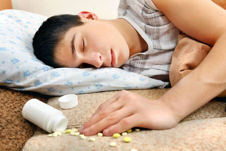 intoxication: Teenager sleeps near the scattered Pills on the Bed at the Home