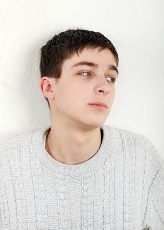 teenager thinking: Adolescente que piensa cerca de la pared en el hogar
