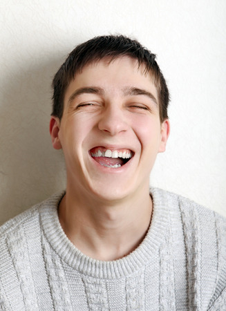 Happy Teenager laughing near the wall at the Home photo