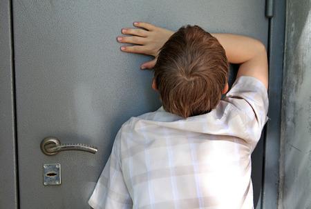 Sad Kid in front of Closed Door photo