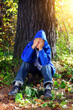sorrowful: Sorrowful Teenager sitting in the Forest Stock Photo