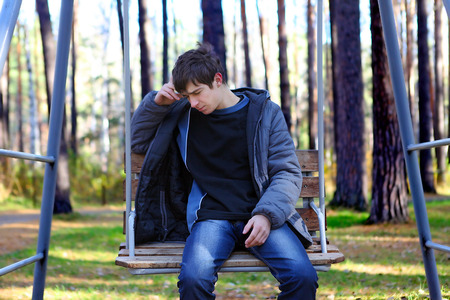 Lonely Sad Teenager sitting in the Autumn park photo