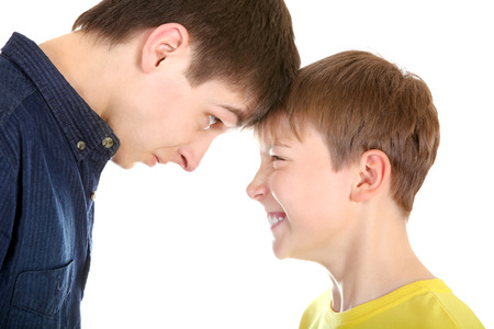 dissension: Teenager and Kid looking to each other on the White Background closeup