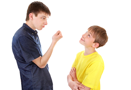 dissension: Teenager threaten a Naughty Kid with a Fist on the White Background