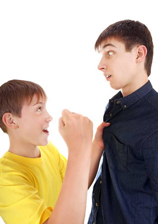 threatens: Kid threatens to Teenager with a Fist Isolated on the White Background Stock Photo
